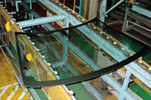 The production process of automotive glass: Where glass is formed into the prescribed shape by applying heat; the black parts are where ceramic is sintered on.