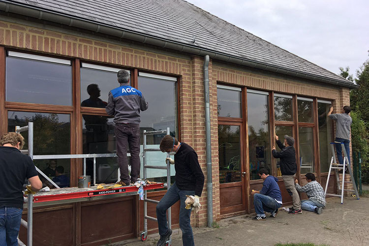 AGC Glass Europe employees power-sand and paint a special school for exceptional children